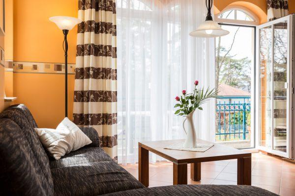 Rügen-Ferienwohnung Strandflair in Baabe - Wohnzimmer mit Couch und Balkon